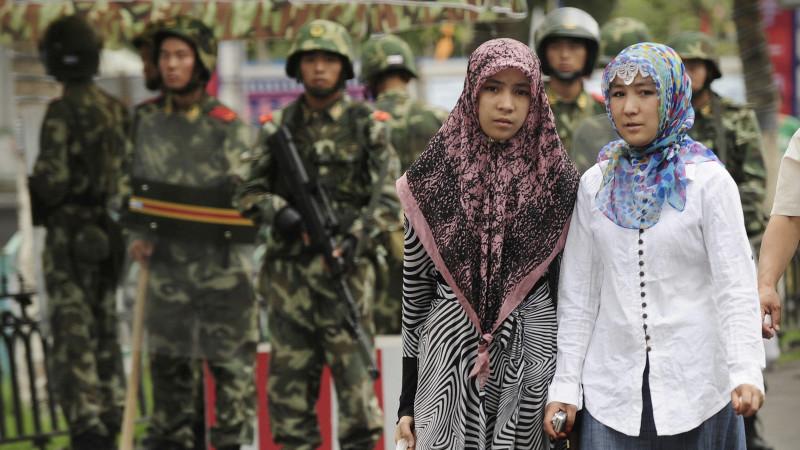 Two ethnic Uighur women pass Chinese paramilitary policemen