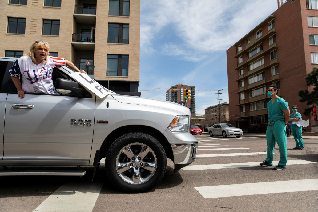 Health care worker blocks a protester's vehicle