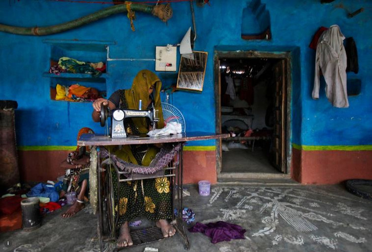 A woman uses a manual seing machine inside her house at Meerwada Village of Guna District in the Central Indian State of Mandhya Pradesh June 19,2012.