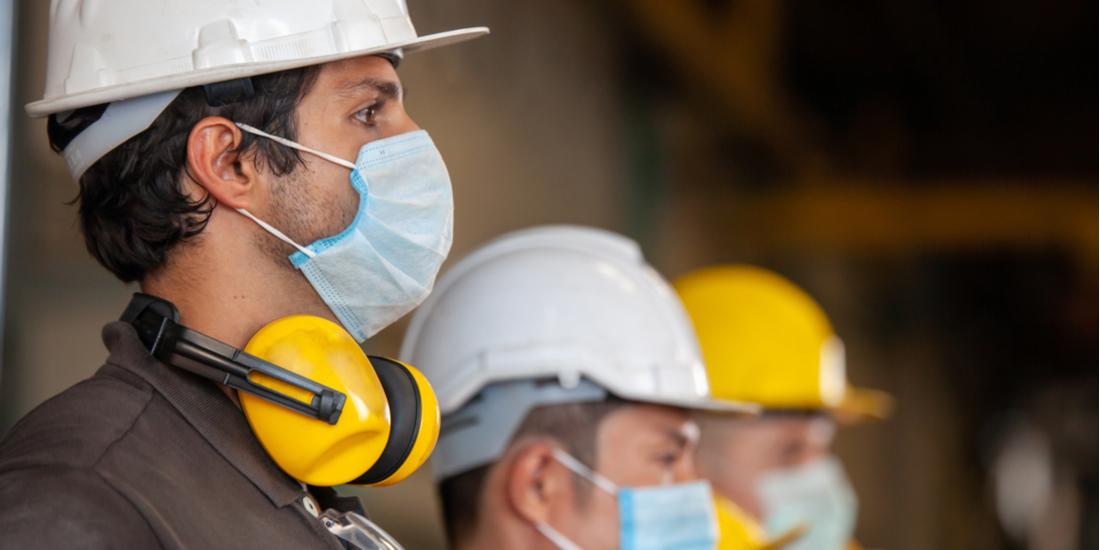 Workers wear protective face masks for safety in machine industrial factory