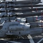 U.S. Marine Corps Huey and Cobra Helicopters sit onboard the USS Peleliu