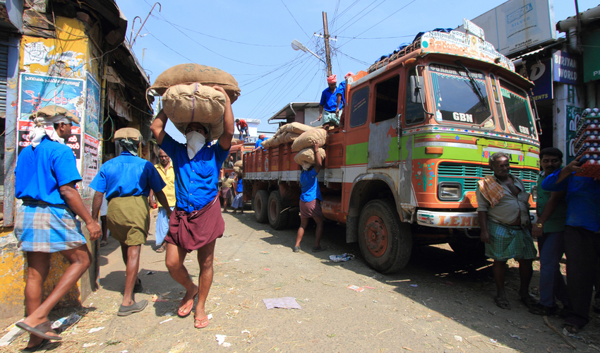Unidentified head load workers unloading gunny bags from a truck in the market