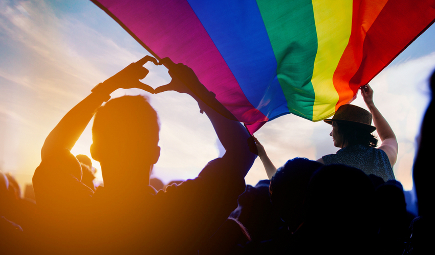 Pride community at a parade with hands raised and the LGBTQ flag
