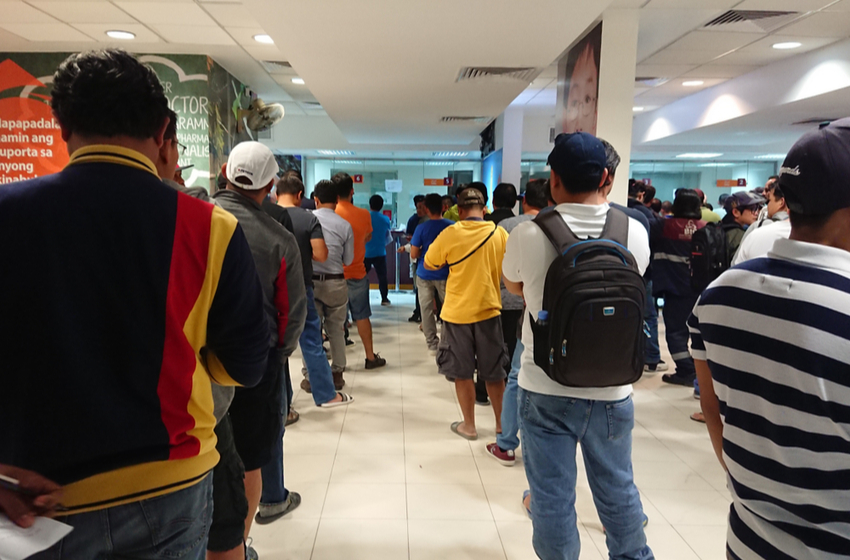 People are waiting in line to remit money via a money transfer service