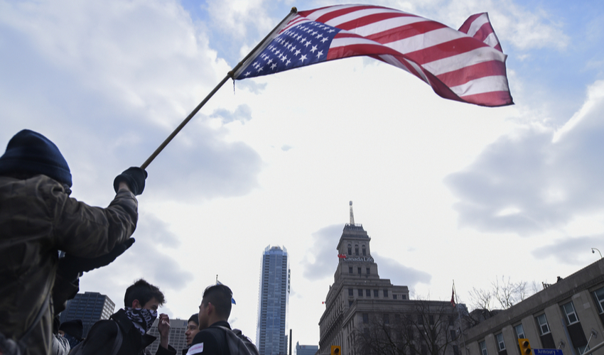 Protesters waiving an American flag during a protest in front of the US Consulate to denounce Donald Trump's immigration policies on February 4, 2017 in Torona