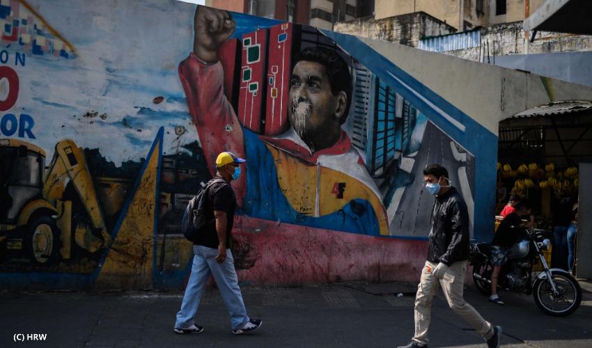 People wearing face masks walk past a mural depicting Venezuelan president