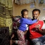 Somali refugee Bader Abdullah Hassan sits with his son, Muhammad, at their house in Sanaa, Yemen
